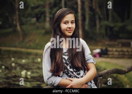 Ritratto di bella ragazza adolescente appoggiata sul ramo in posizione di parcheggio Foto Stock