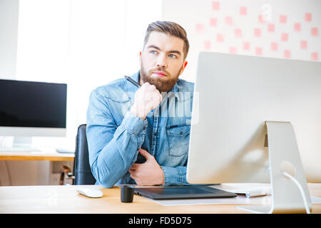 Malinconici attraente e moderno designer seduto sul posto di lavoro in ufficio e pensare Foto Stock