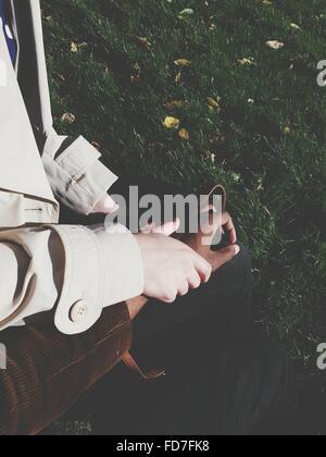 Immagine ritagliata della giovane tenendo le mani sul campo erboso Foto Stock