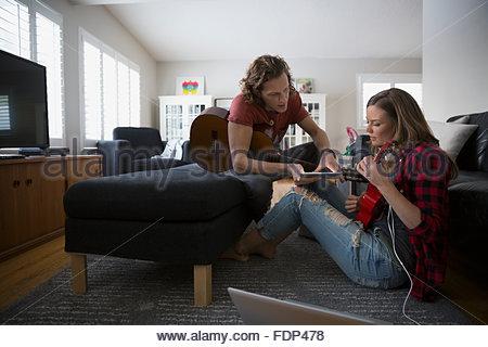 Coppia con tavoletta digitale a suonare la chitarra e ukulele Foto Stock