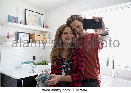 Giovane tenendo selfie in cucina Foto Stock