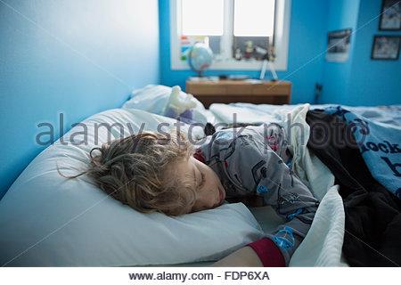 Bambino addormentato nel letto Foto Stock