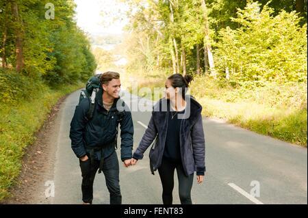 Giovani escursionismo coppia tenendo le mani sulla strada rurale Foto Stock