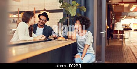Ritratto di tre giovani seduti insieme a un cafe'. Un gruppo di giovani amici riuniti in una caffetteria. Foto Stock