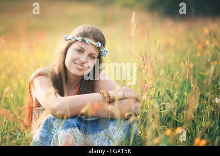 Sorridente donna romantica nel campo dei fiori . Hippie e gypsy dress Foto Stock