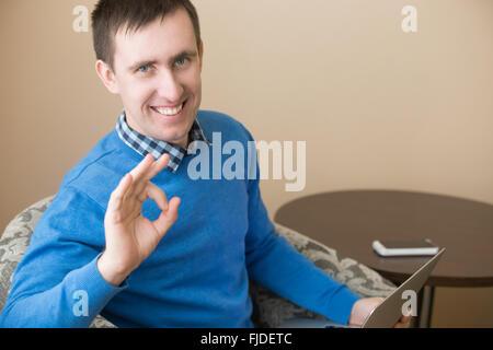 Ritratto di casual attraente felice giovane uomo che pongono in interni, seduti in poltrona con laptop, gestualità Foto Stock