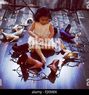 Ragazza seduta nel mezzo di tacchi alti e le luci di Natale sul pavimento di legno duro Foto Stock