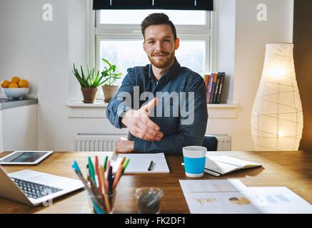 Imprenditore sorridente appoggiata in tutta la sua scrivania che offre la sua mano nel saluto, per chiudere una Foto Stock