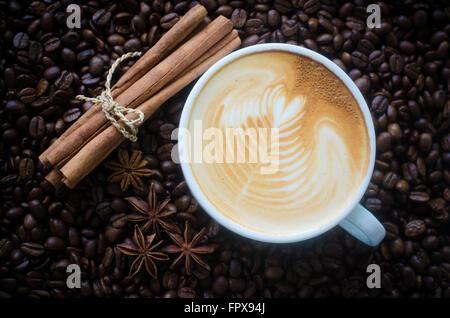Una tazza di latte art sul chicco di caffè sfondo Foto Stock