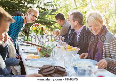 Tre generazioni della famiglia gustando un pasto all'aperto. Foto Stock