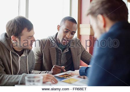 Amici di sesso maschile in discussione a pranzo Foto Stock