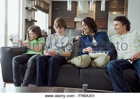 La famiglia sul lettino impegnato con la tecnologia Foto Stock