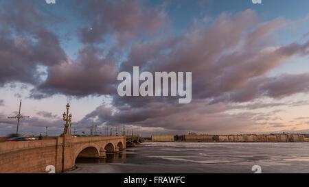 La Russia, San Pietroburgo, 19 marzo 2016: Rosa nuvole sopra il ponte Troitsky al tramonto, drifting ice, congelati Foto Stock