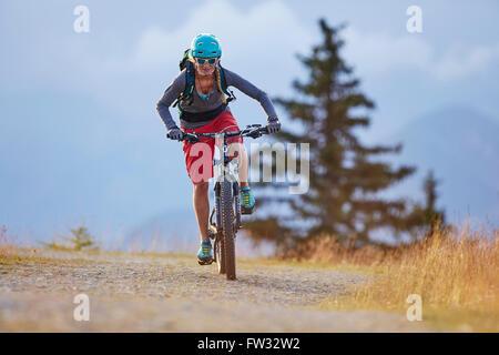 Mountain biker con un casco a cavallo su una strada di ghiaia, Mutterer Alm vicino a Innsbruck in Tirolo, Austria Foto Stock