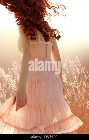 Curly donna allontana Foto Stock