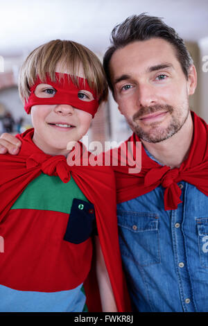 Ritratto di padre e figlio fingendo di essere il supereroe in salotto Foto Stock