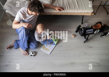 La Svezia, Padre e figlio (12-17 mesi) seduto sul pavimento nel soggiorno Foto Stock