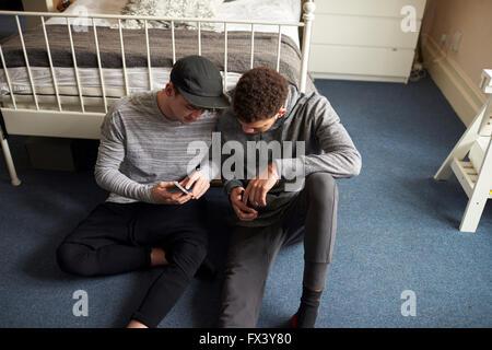 Due gli studenti maschi in camera da letto controllare i messaggi su telefoni cellulari Foto Stock
