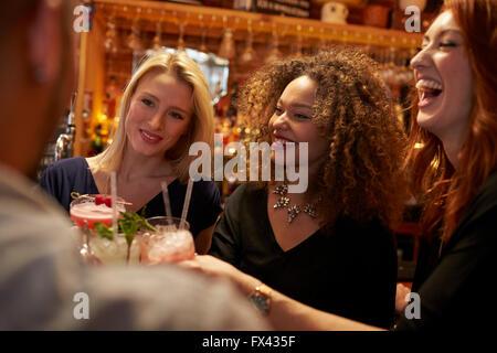 Gruppo di amici riuniti per un drink serale nel Cocktail Bar Foto Stock