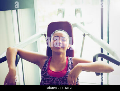 Stanco donna appoggiata con attrezzature per esercizi in palestra Foto Stock