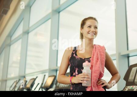 Donna sorridente in appoggio e acqua potabile in palestra Foto Stock