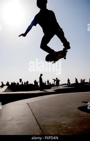 Guidatore di skateboard in midair a skate park Foto Stock
