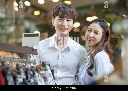 Giovane con lo sguardo in avanti con un sorriso in negozio Foto Stock