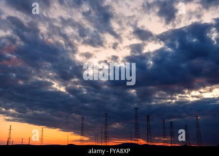 Alta tensione delle linee di trasmissione su arancio e blu cielo Foto Stock