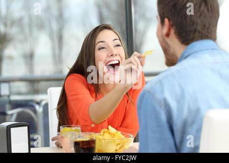 Giocoso giovane mangiare patate di chip e scherzando cercando reciprocamente in una data in un coffee shop Foto Stock