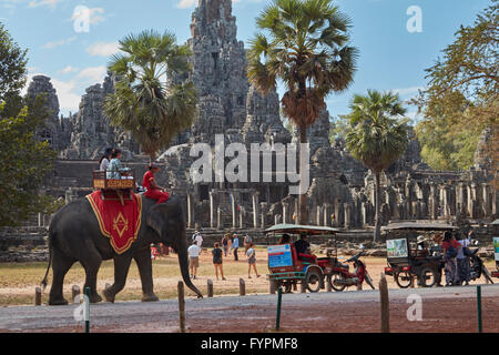 I turisti su elefante,tuk-tuks e tempio Bayon rovine, Angkor Thom (XII secolo complesso tempio), Angkor Sito Patrimonio Foto Stock