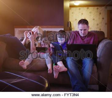 Una famiglia moderna è insieme seduta su un divano a casa con la tecnologia compresse per un intrattenimento o il Foto Stock
