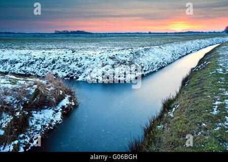 Tramonto su prati di inverno Foto Stock