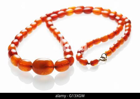 Stringa di antichi cordoni di ambra per uso come una collana su un bianco sfondo riflettente Foto Stock