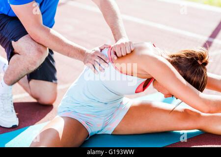 Trainer aiutando durante strech fuori all'aperto shot Foto Stock