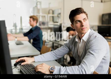 Bel giovane studente utilizzando il computer in aula Foto Stock