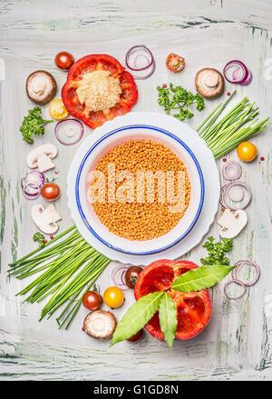 Di lenticchie rosse nella ciotola e verdure ingredienti per una sana cucina vegetariana, vista la composizione. Foto Stock