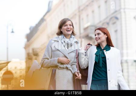 Donna sorridente il trasporto delle borse della spesa in città Foto Stock