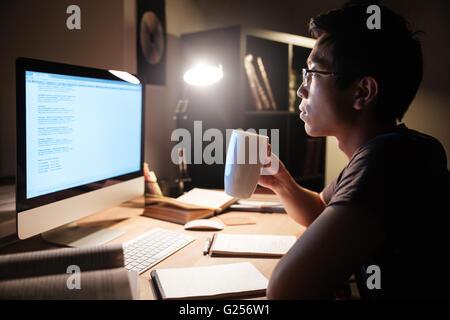 Profilo di bello asian giovane studiando con computer e bere il tè in camera oscura Foto Stock
