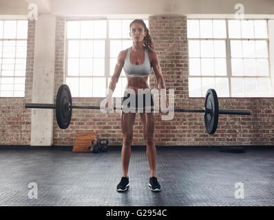 Lunghezza completa immagine di duro giovane donna esercitando con barbell. Determinato atleta femminile di sollevamento Foto Stock