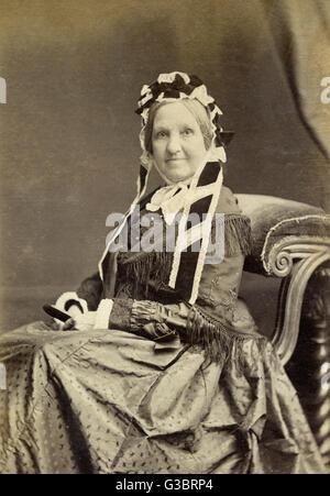 Di mezza età vittoriana di donna in un ritratto in studio, sorridente alla fotocamera. Data: circa 1860s Foto Stock