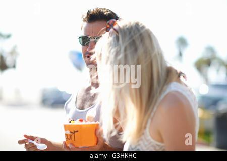 Paio di passeggiare e mangiare yogurt surgelato, Venice Beach, California, Stati Uniti d'America Foto Stock