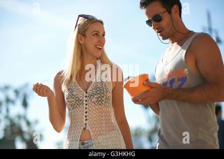 Paio di passeggiare e mangiare yogurt surgelato a Venice Beach, California, Stati Uniti d'America Foto Stock