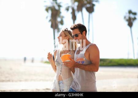 Paio di passeggiare e la condivisione di yogurt surgelato a Venice Beach, California, Stati Uniti d'America Foto Stock