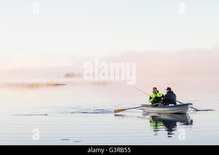 La Svezia, Vastmanland, Bergslagen, Torrvarpen, giovani uomini la pesca nel lago al tramonto Foto Stock