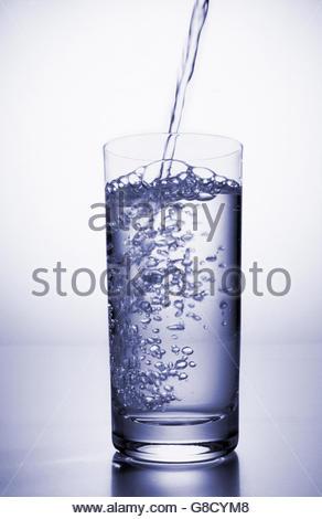 Vista dell'acqua versata in un bicchiere Foto Stock