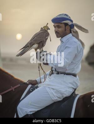 Un cacciatore montato a cavallo con la sua falcon all'alba durante il Galayel al Festival di caccia in Qatar. La Foto Stock