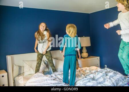 Ragazza adolescente di saltare sul letto con i fratelli più giovani Foto Stock