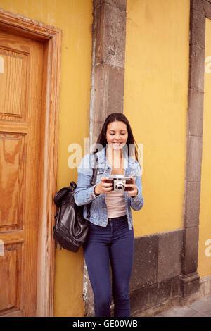 Ragazza giovane e carina appoggiata contro un pilastro grigio sorridente alla sua fotocamera con vecchi edifici Foto Stock