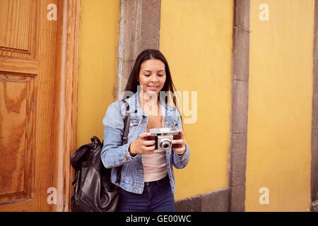 Ragazza giovane e carina appoggiata contro un pilastro grigio osservando la sua fotocamera con vecchi edifici gialli Foto Stock
