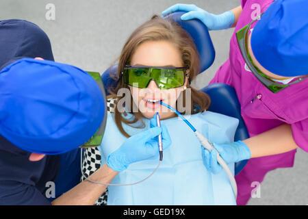 Dentista utilizzando laser sbiancante su un paziente femmina Foto Stock